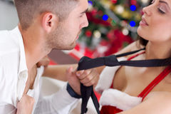 Sexy female Santa seduces man on Christmas night Stock Photo