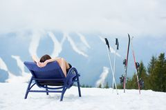 Sexy female skier on blue deck chair near skis at ski resort Stock Photography