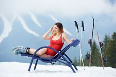 Sexy female skier on blue deck chair near skis at ski resort Royalty Free Stock Image