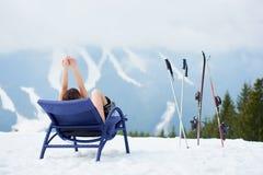 Sexy female skier on blue deck chair near skis at ski resort Royalty Free Stock Photo