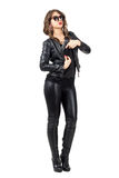 Sexy female spy wearing leather clothes pulling handgun from her jacket. Stock Images