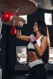 Sexy fighter girl punching actively. Strong athletic woman with boxing pear Royalty Free Stock Images