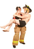 Firefighter rescues a handsome man. Female firefighter rescuing a grateful handsome man royalty free stock images