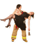Sexy fireman rescuing pretty woman Royalty Free Stock Photos