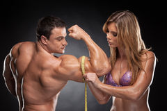 Sexy fit blond woman measure hand male  muscular. Royalty Free Stock Photography