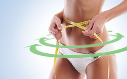 Sexy and fit femaly body. The woman is measuring her waist Royalty Free Stock Photography