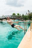 Sexy young man  jumping in the swimming pool in a resort. Sexy fit man jumping in the swimming pool in a resort Stock Photos