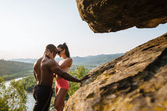 Sexy fit mixed race couple with perfect bodies in sportswear posing on the rocky mountains landscape. Full-length fashion portrait, sport and lifestyle concept Stock Image