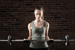 Sexy fit woman lifting dumbbells on brick background Royalty Free Stock Photos