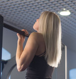 Sexy fit woman performing pull ups in a bar Stock Image
