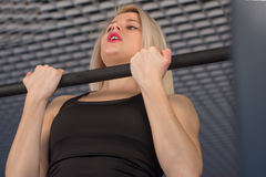 Sexy fit woman performing pull ups in a bar Royalty Free Stock Image