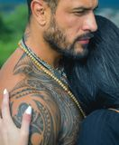 Sexy and fit woman and hugging handsome man with tattoo. Passion and sensual touch. Young couple in love hug each other