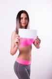 Sexy fitnes Brunette in einem Trainingsnazug, der leeres weißes Brett hält Stockfotografie