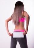Sexy fitnes brunette in a tracksuit holding empty white board Stock Image