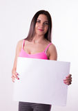 fitnes brunette in a tracksuit holding empty white board Royalty Free Stock Photo