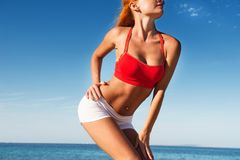 Sexy fitness. Sensual female body wearing fitness outfit by the sea Royalty Free Stock Images