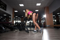 Fitness beautiful young girl resting after squat exercises royalty free stock photography