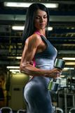 fitness brunette woman is doing biceps curls with dumbbells in the gym royalty free stock photo