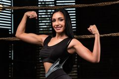 Fitness brunette woman is standing near the box ring and showing biceps. Fitness brunette woman is standing near the box ring, relies on ropes, resting and stock photography