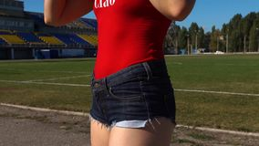 Fitness Female Warming Up Before Training. Hot Fitness Female Wearing Red Swimsuit and Jeans Shorts Warming Up Before Outdoors Training stock video