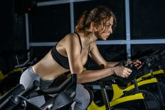 Sexy young woman has spinning exercising at the fitness gym. stock photos