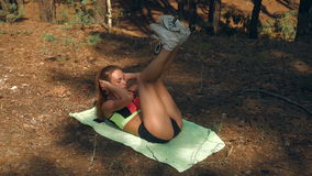 fitness girl lies on her back by lifting the legs with the Dumbells above and shakes press