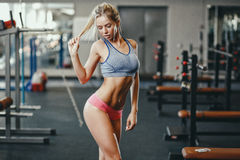 Sexy fitness happy blonde girl in sport wear with perfect body in the gym posing and smiling. Sexy fitness happy blonde girl in sport wear with perfect body in Royalty Free Stock Photos