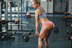 Sexy fitness happy blonde girl in sport wear with perfect body in the gym posing and smiling. Sexy young athletics blonde girl doing deadlift with barbell Stock Image