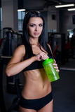 Sexy fitness woman in sportswear resting after dumbbells exercises in gym. Beautiful girl with perfect fitness body drinking from. Shaker bottle after gym Stock Photos