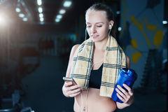fitness woman in sportswear resting after dumbbells exercises in gym. Beautiful girl with shaker and towel. royalty free stock images
