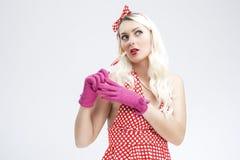 Sexy Flirtpinup-kaukasische blonde Frau mit roter süßer Süßigkeit Stockfoto
