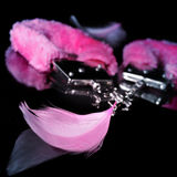Sexy fluffy handcuffs and feathers used as adult toys. A pair of pink sexy fluffy handcuffs and some pink feathers used as adult toys on a reflecting black Stock Photos