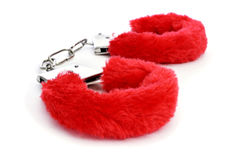 Sexy fluffy handcuffs. A pair of red sexy fluffy handcuffs on a white background Royalty Free Stock Photos