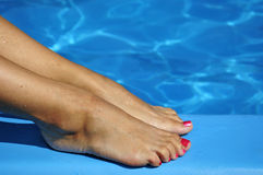 Sexy foot on swimming pool. Pretty women foot with blue water background Stock Photo