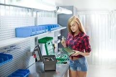 Sexy Frau in überprüftem Hemd mit elektronischer Platte in einer Garage Stockbild