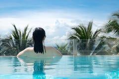 Sexy Frau in der Bikinischwimmenklage, die im Luxuspool sich entspannt stockbilder