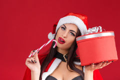 Sexy Frau in der Kleidung von Santa Claus mit Weihnachtssüßigkeit Stockbilder