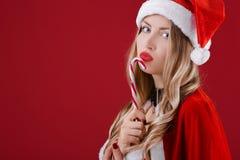 Sexy Frau in der Kleidung von Santa Claus mit Weihnachtssüßigkeit Lizenzfreie Stockbilder