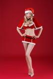 Sexy Frau in der Kleidung von Santa Claus mit Weihnachtssüßigkeit Lizenzfreies Stockfoto