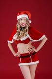Sexy Frau in der Kleidung von Santa Claus mit Weihnachtssüßigkeit Lizenzfreie Stockfotografie
