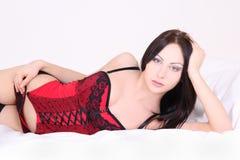 Sexy Frau in der roten Wäsche, die auf Bett liegt Lizenzfreie Stockfotografie