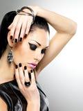 Sexy Frau der schönen Mode mit schwarzen Nägeln am hübschen Gesicht Stockfoto