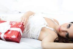 Frau in der weißen Wäsche, die auf einem Bett mit rotem Geschenk liegt Lizenzfreie Stockfotos