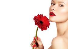 Sexy Frau des Nahaufnahmeschönheits-Fotos mit den roten Lippen, Lippenstift und schöner roter Blume Saubere Haut des Badekurortes Lizenzfreie Stockfotos