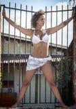 Sexy Frau, die am alten Tor steht Stockfoto