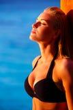 Sexy Frau, die auf dem Strand sich bräunt Lizenzfreie Stockbilder