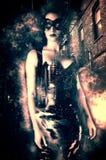 Sexy Frau, die eine venetianische Maske und ein festes Latexkostüm in einer dunklen Stadtgasse trägt Stockfotos