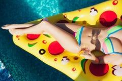 Sexy Frau, die Getränke am Pool, 20s genießt Stockfotografie