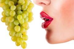 Sexy Frau, die grüne Trauben, sinnliche rote Lippen isst Lizenzfreies Stockfoto
