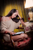 Sexy Frau, die im hölzernen Stuhl sitzt und in einer Weinleseszene liest Stockfotografie